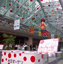 Photo of a glass roof decorated with red dots, from which hangs a green swing with a doll/ child figure in a red dress with white polka-dots. She has yellow skin also with white dots, blue and black spotted shoes and a black and red spotted pudding-basin