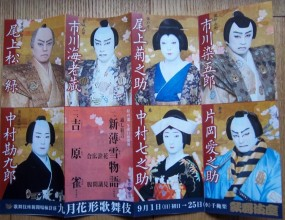 Colourful photo of the promotional leaflet featuring close-up portraits of the seven main actors in costume, wigs and the traditional white face, red and black make-up.