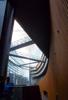 Photographic view into the glass atrium of Tokyo International Forum from the accessible end. There are the wooden slats on the right and a dark ceiling against a bright triangle of glass filtered light.