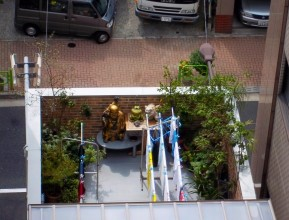 Photograph looking down into a small walled balcony/roof garden. Left and right are trees and plants, against the far wall are two tables with a golden Buddha, and two other statuettes of spiritual entities. They share the space with lines of washing.