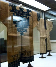 Photo of two garments displayed in a glass case. There is a bad reflection on one, from light on the glass. The garments are a simple shape if coat displayed with a rod through the armholes. They are of a course, hemp-type fabric, in a natural 'dry-grass'