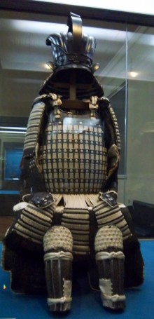 Photograph of black and white woven leather armour in Tokyo National Museum. Displayed in a glass case, it looks like a seated figure in a helmet. Only the absent face, fingers and feet reveal that it is empty.