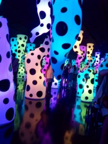 Colourful image of protruding, twisted, sausage-balloon-like shapes on a black background, this is Kusama Yayoi's Love is Calling displayed in a mirrored room where the black dots on each shape are constant, but the colours are frequently changing. Here t