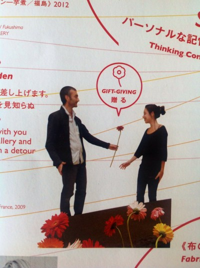 From the poster for the exhibition, this image shows the artist handing over a Gerbera to a female recipient. There is a text bubble with the words 'gift-giving