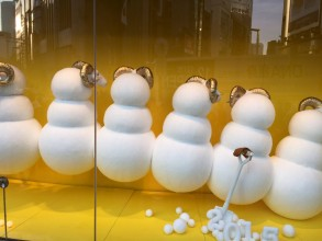 The white sheep in the Wako department store window sit on white balls, like giant snowballs, with there backs to the audience. The golden curls of their horns and the yellow-gold setting are the only colour.