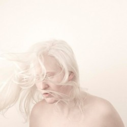 Photograph of Artist Jo Bannon is naked, shown from the shoulders upwards against a pale background with her white hair being blown forward.