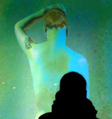 Portrait of a figure looking at an artwork depicting the back of a woman