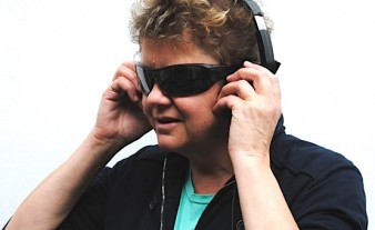 photo of performer Julie McNamara wearing headphones and dark glasses