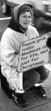 Photograph of an elderly woman sitting on a box holding up a sign saying: 'Please give today. Madness is for life, not just for Christmas'