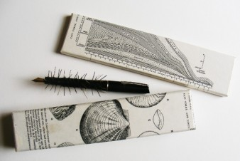 an artwork by jon adams shows a black pen with barbs attached and two halves of a decorated box Jon Adams