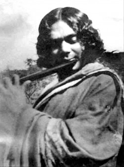 sepia photo of the poet Nazrul playing a flute