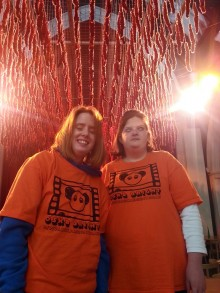Becky and Adele stand beneath an art installation made of red wool