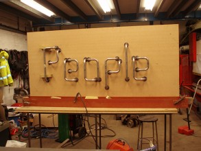 Bright metal grab rails screwed onto a large board and spelling the word 'People' on display in the Ozweld workshop