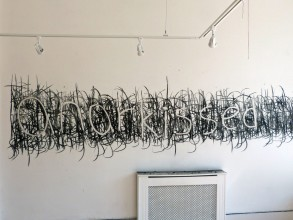 the word 'anarkissed' written in a scrawling, heavy black and white hand across a white gallery wall