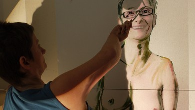artist stands in front of self-portrait