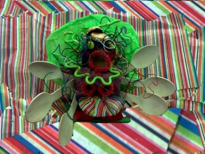 a female figure made of modelling clay (similar to Plasticine), pipe cleaners, wooden spoons, lolly sticks, bendy wire and wrapping paper floats against a brightly coloured stripy background