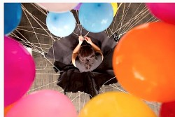 The artist Noëmi Lakmaier is photographed from above with several inflated coloured helium balloons