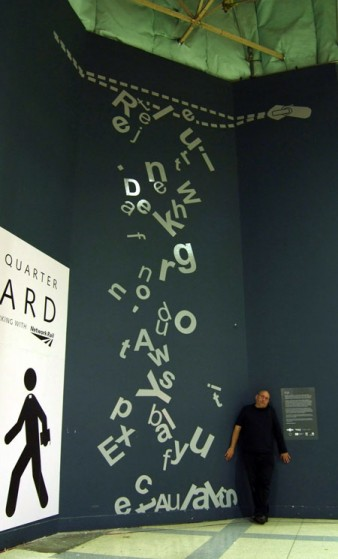 Artist Jon Adams standing next to his WordWall installation at London Bridge station.