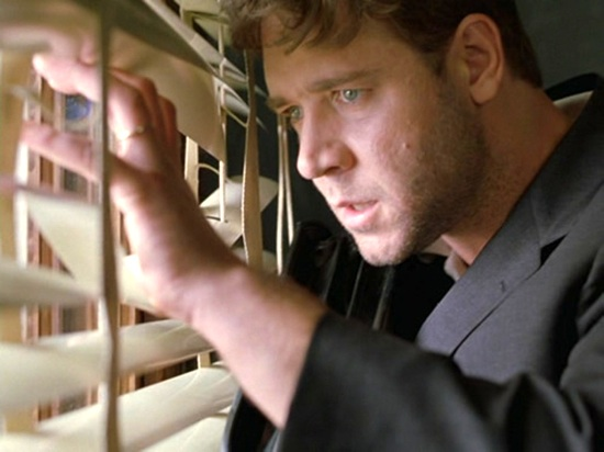 film still in which actor Russell Crowe is portrayed looking anxiously through a set of blinds