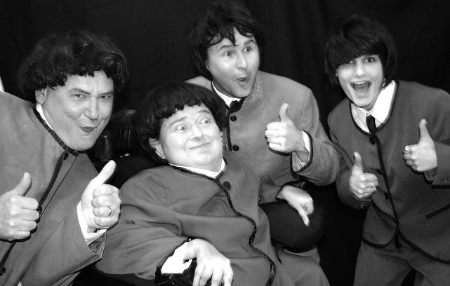 black and white photo of 4 performers posing as the Beatles