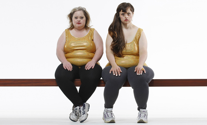 photo of two actresses, sitting facing the camera, dressed in tight yellow, plastic tops , black tights and white sneakers