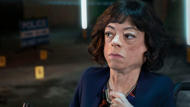 A photograph of Liz Carr as Clarissa Mullery in the BBC's Silent Witness. The image is a close up on her face with a crime scene in the background.