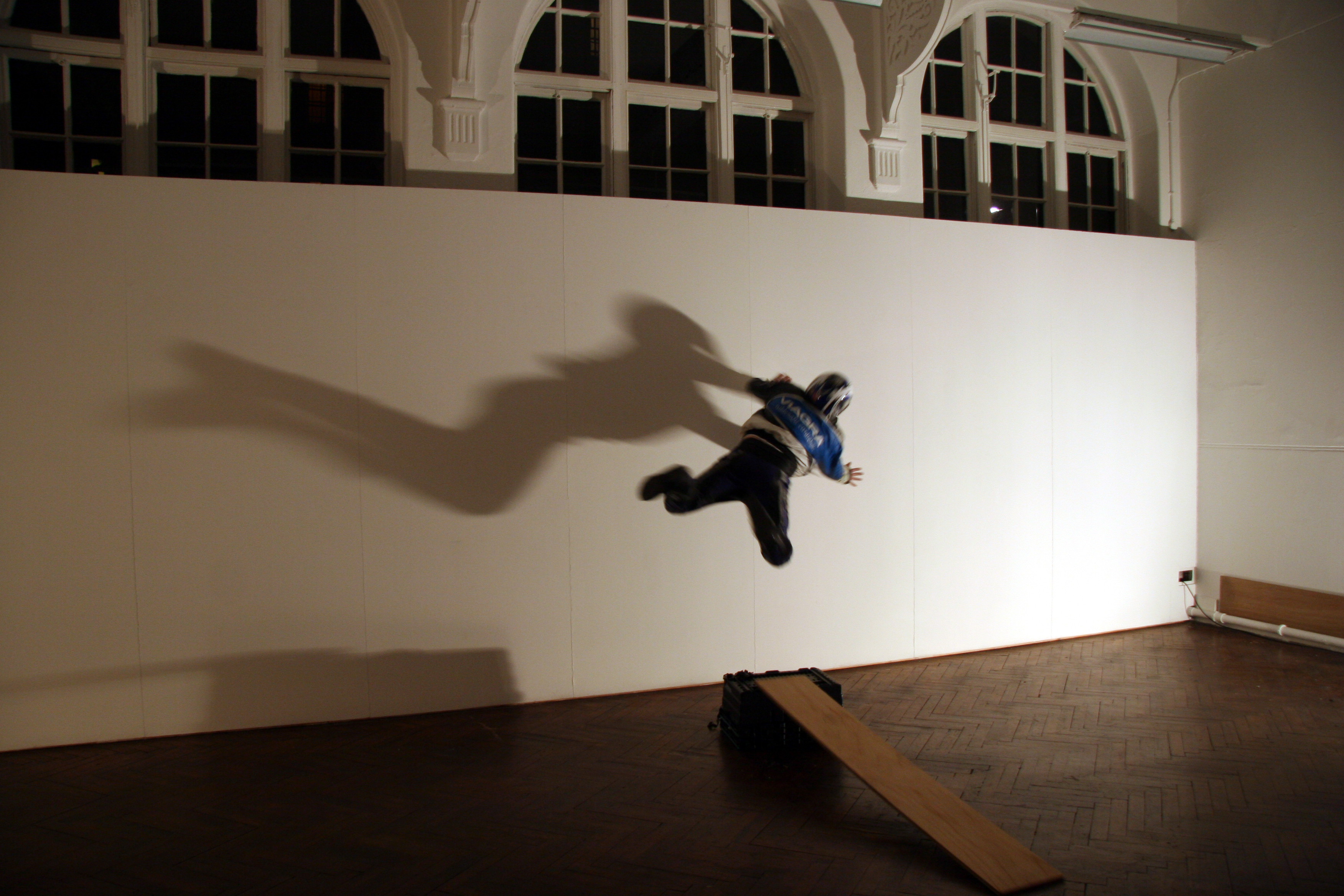 artist launches himself against a white wall with windows above