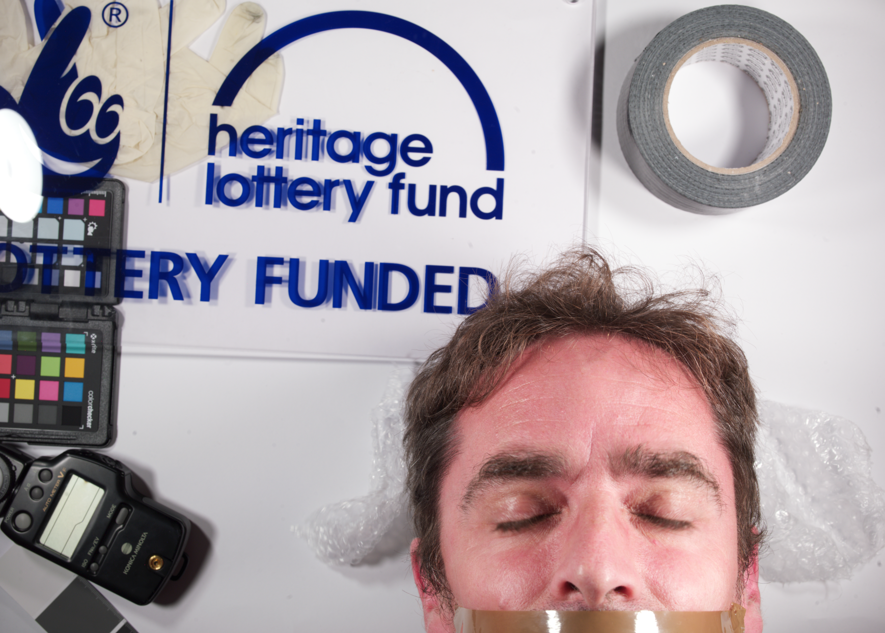 A selfie taken with a special Rostrum Camera of NDACA archivist Alex Cowan, he has tape around his mouth and his eyes closed, with detritus surrounding him