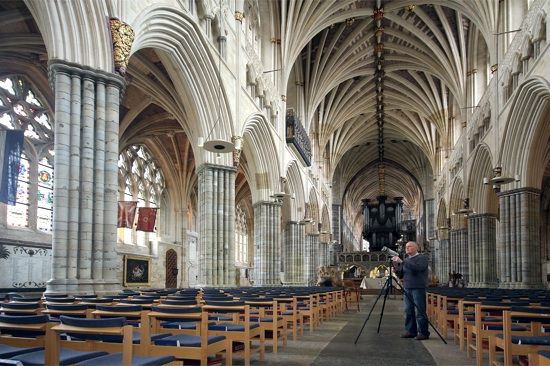 photo of a man standing looking into a camera, inside Exeter cathedral