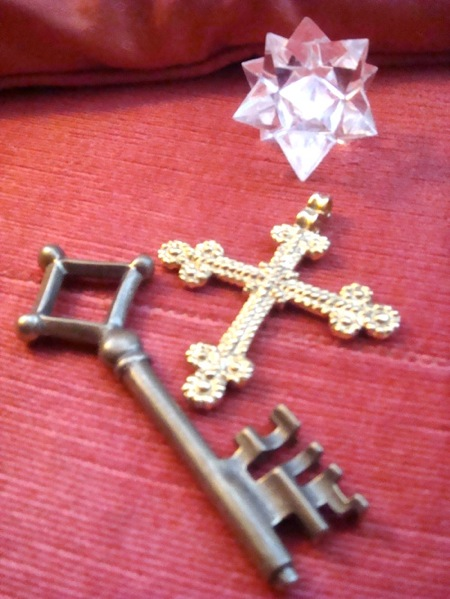 picture of an old key, a gold cross and and white crystal against a red backgorund