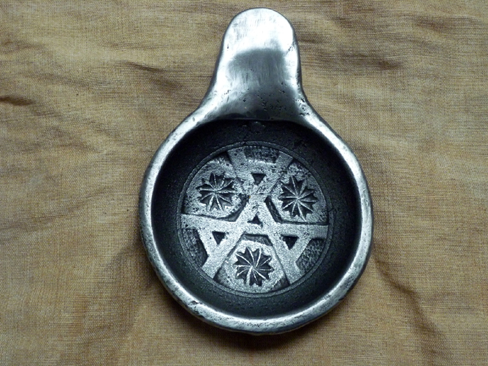shows a metal bowl with interlocking 'A' symbols in the centre