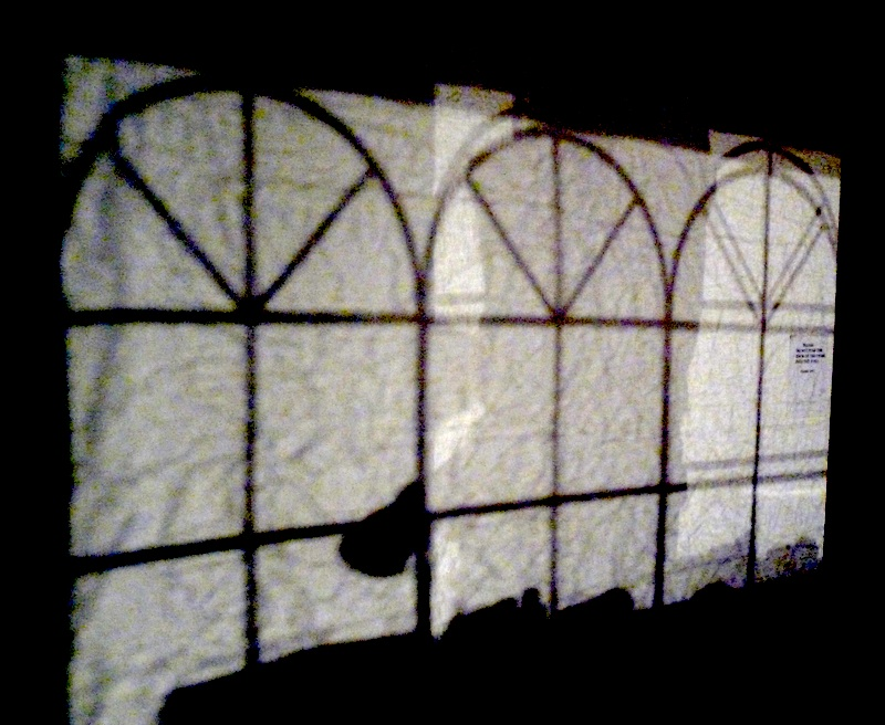 photo of a series of three windows with a blind in front of them