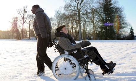 film still of a man dragging a wheelchair-user backwards through thick snow