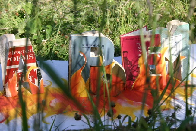 photo of a series of painted and carved books in amongst some grass