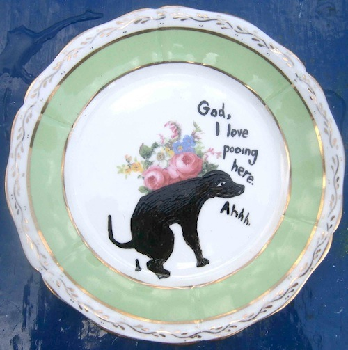 decorated china plate with paining of a dog pooing