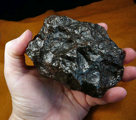 Photo of a hand holding a lump of rock from a meteorite