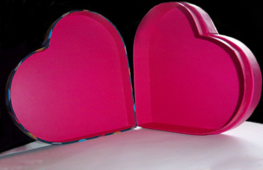 close-up photo of the inside of an open heart-shaped box. The box is bright pink, the background black and white