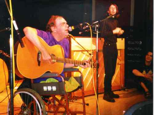 Ian Stanton sings and plays guitar, with a BSL interpretor.