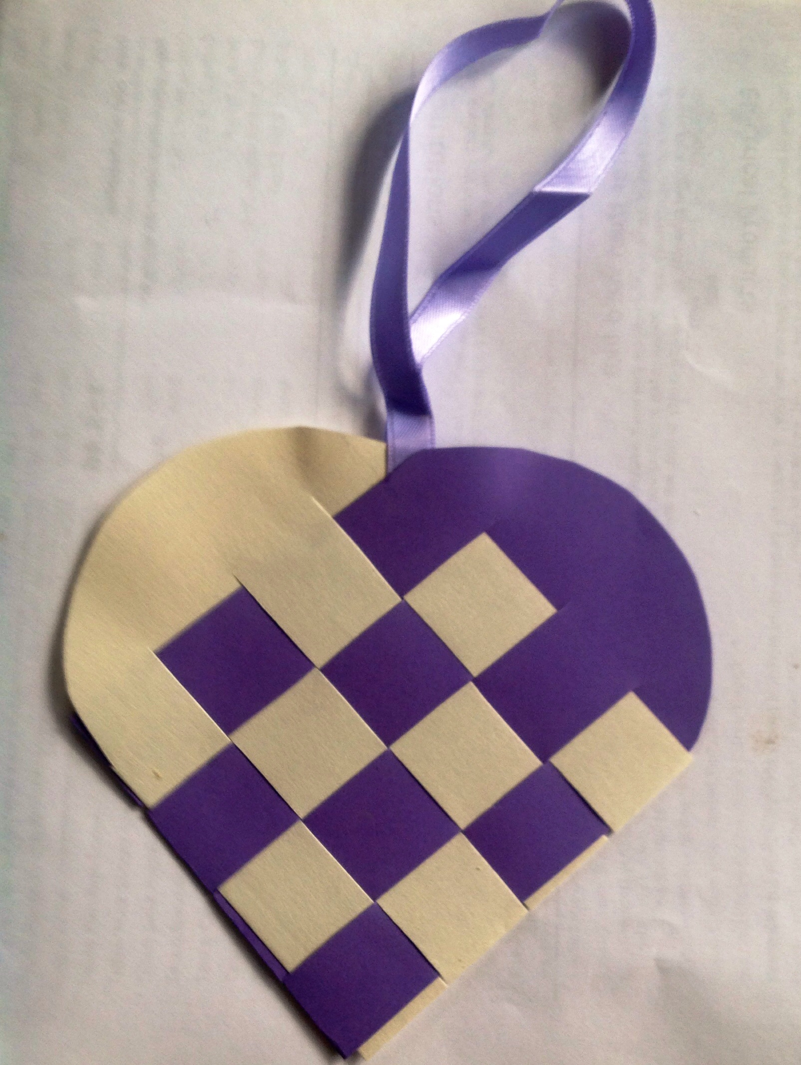 Purple and cream paper cut and plaited into a heart-shaped container with a thin purple ribbon handle to hang it up with; a traditional Danish tree decoration.