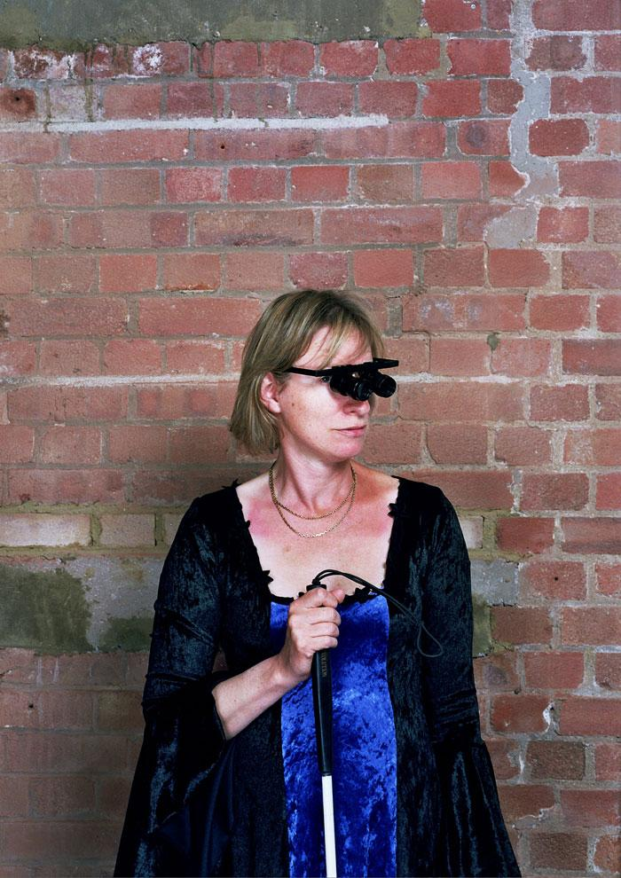 photo of performer Liz Porter, wearing sight aids and carrying a white cane, set against a red brick wall