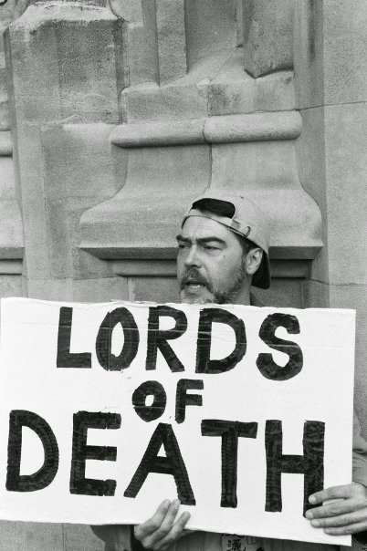 Activist from Disabled People's Direct Action Network holds placard outside House Of Lords reading 'Lords of Death'