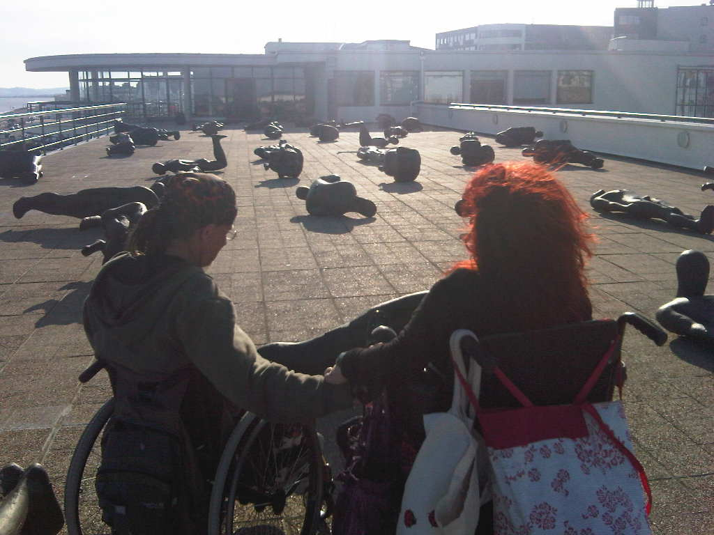 photo of two wheelchair-users on a seaside prom