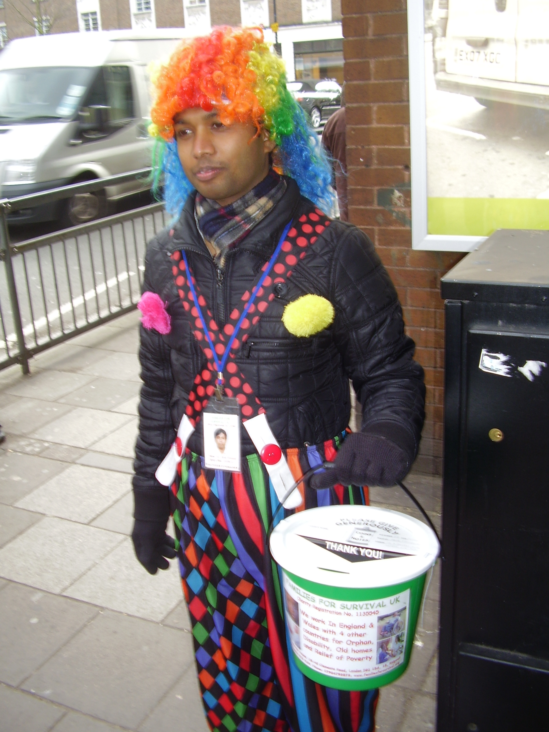 photo of a man with a charity collecting bucket dressed in clown or harlequin outfit