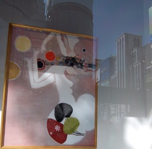 Semi abstract picture of a woman drawn with Chinese ink and pigments, in a slim wooden frame, seen with reflected city-scape in shop-window..
