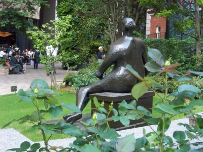 Viewed from behind, Henry Moore's bronze of a seated woman looks into Brick Square, where shoppers find a small haven of green peace.