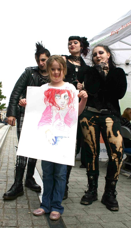 photo of a young girl holding up a painting in front of a group of young people