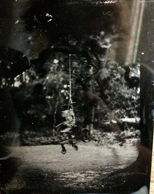 wet plate image of a wheelchair hanging in a tree