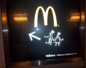 This is a Japanese advert for MacDonalds with two stick figures under the M, a pointing arrow and some Japanese text