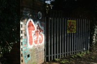 Photo of a set of railings with a yellow warning sign.Part of a graffitied brick wall takes up the left hand third of the image