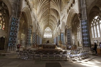 photo of the inside of Exeter cathedral with artists banners hanging down from the central columns
